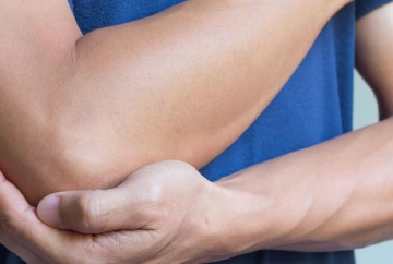 Photograph of person holding elbow because of pain