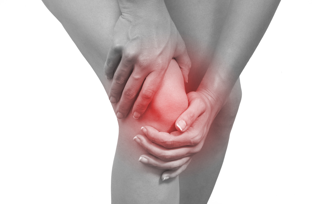 Person holding their knee because of pain